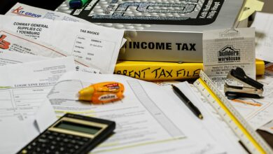 Auf einem Tisch befinden sich Steuerbücher, ein Taschenrechner und Rechnungen